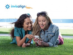 Two girls laying on grass looking at a phone