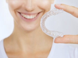 Woman holding an Invisalign retainer
