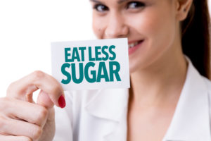 Woman holding a sign that says eat less sugar