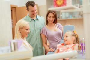 Family with one child at the dental office talking to a dental hygienist