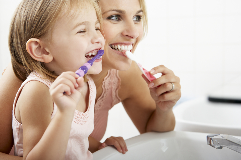 mother brushing her teeth with her daughter