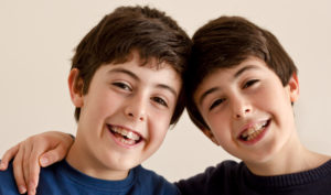 Two young boys that both have braces on their teeth