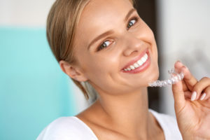 Woman smiling and holding her Invisalign aligners