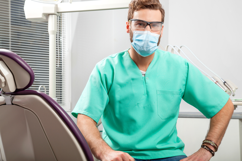 Orthodontist in his scrubs and face mask in an orthodontic office