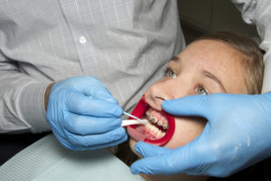 Young girl having her braces adjusted by an orthodontist