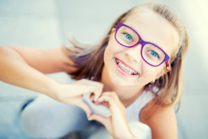 Young girl making a heart shape with her hands and smiling with her braces.