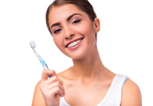 Young adult woman that is holding a toothbrush and has braces on her teeth.