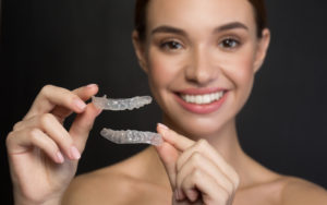 Brunette woman smiling and holding transparent orthodontic aligners.
