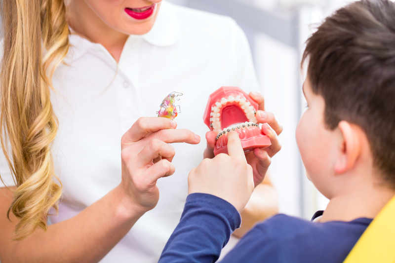 Orthodontic professional showing a patient a model of a mouth that has two different types of braces on it.