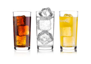 A soda, sparkling water and juice in three separate glass cups all lined up in a row on a white background.