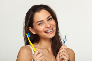 A beautiful brunette teen that has braces on her teeth and that is holding a toothbrush and interdental brush in her hands.