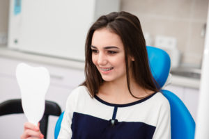 A young brunette teen girl that has just gotten braces on her teeth and is smiling at her reflection in a mirror at the dental office.