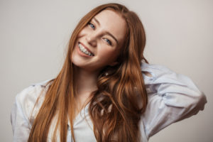 A redheaded young adult that is smiling and tilting her head. She has braces on her teeth.