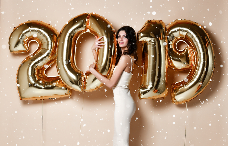 "Large gold balloons that say ""2019"". There is a beautiful brunette woman standing in the middle of the zero and one that is smiling at the camera."