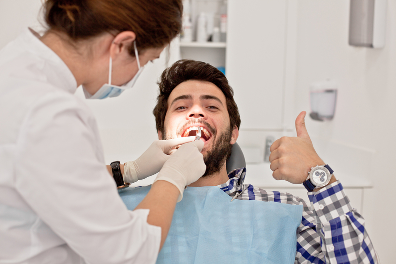 A young adult male that is having his teeth examined by a dental hygienist.