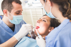 A young adult woman that is having her teeth and gums looked at by both a dental hygienist and dentist.