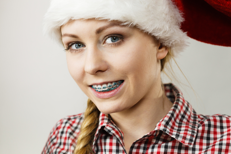 A young, blond teenager that is smiling at the camera and wearing a Santa Claus hat. She has metal braces on her teeth to get a better smile.