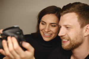 An image of a young adult male and female that are taking a photo together. The female has clear, ceramic braces on her teeth to get a better smile during the holidays.