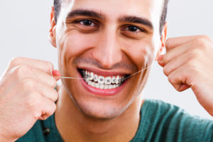Man flossing braces and smiling