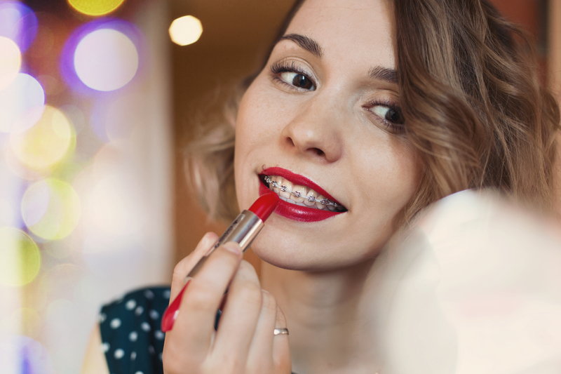 A brunette woman putting on red lipstick as she gets ready for a New Year's Party. She is wearing ceramic braces on her teeth.