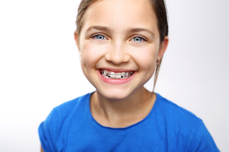 Young girl smiling and wearing braces