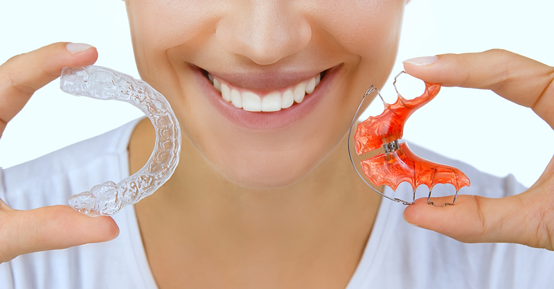 Woman holding two types of retainers for the mouth