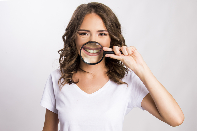 Young woman holding magnifying glass over mouth to show gap between teeth