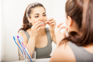 Woman putting whitening stripes on teeth while looking in the mirrow