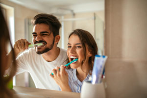 A man and woman brushing their teeth in front of a mirror together