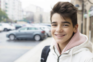 Young male teenager smiling on the street with braces