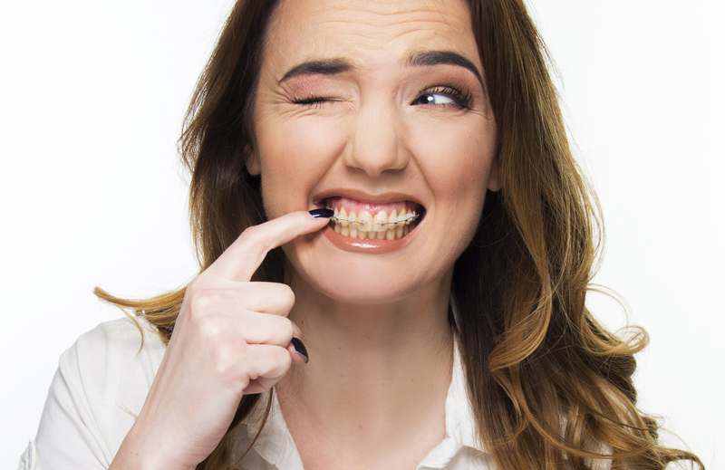 Young woman pointing to braces with a questionable look on her face.