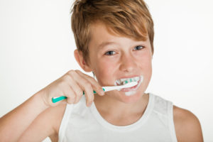 Young boy brushing teeth while smiling