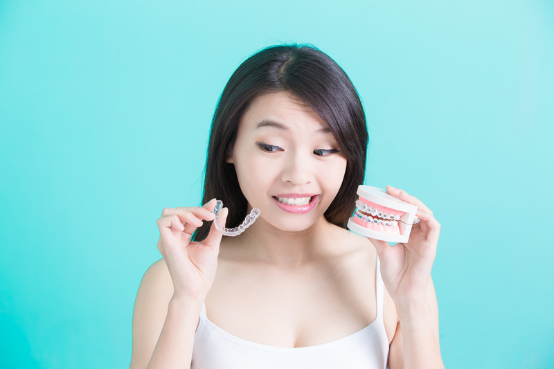Woman holding Invisalign retainer in one hand with an impression of a mouth in the the other
