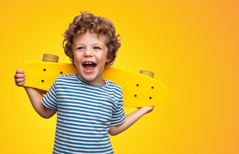 Smiling little boy holding a yellow skateboard on a yellow background