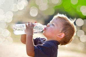 Blonde little boy drinking water from a water bottle