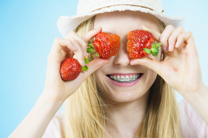 Young woman with braces playing with strawberries and covering her eyes with them